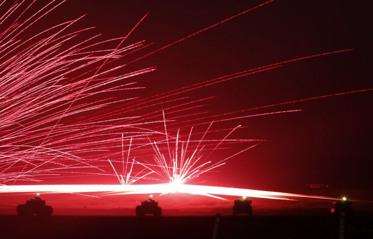 Tracer bullets ricochet off their targets as Japanese Ground Self-Defence Force tanks fire their machine guns during a night session of an annual training exercise at Higashifuji training field near Mount Fuji in Gotemba, west of Tokyo, August 19, 2014. Japanese battle tanks, helicopters and elite troops stormed the foothills of Mount Fuji Tuesday in a first-of-its-kind display of the tactics and equipment the nation's military could use to defend or retake islands in and around the East China Sea. (REUTERS/Yuya Shino)