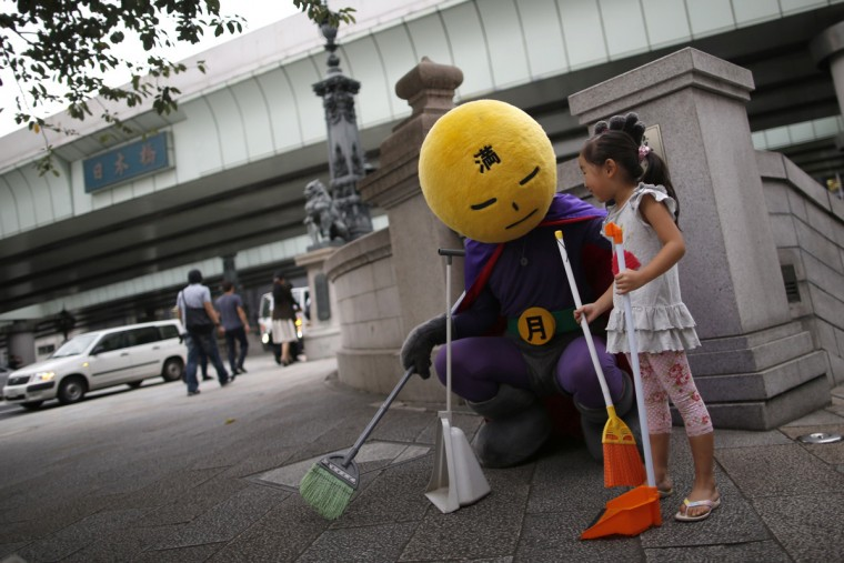 """An unidentified man, who calls himself Mangetsu-man (Mr. Full Moon), pauses as he cleans Nihonbashi bridge using a broom with a volunteer, while clad in a costume featuring a full moon for a head, in Tokyo August 25, 2014. While most superheroes fight crime, for one such Japanese hero the enemy is garbage and his """"super"""" weapons are a broom, a dust pan and an army of volunteers who have joined his mission. Calling himself Mangetsu-man, he first appeared on the streets of Tokyo last year without any publicity or fanfare and mainly cleans around the city's Nihonbashi bridge. Historically, Nihonbashi bridge is Tokyo's most famous bridge until an expressway was constructed over it shortly before the 1964 Tokyo Summer Olympics, and ruined what was for many its iconic status. Mangetsu-man is one among many who are petitioning for the government to get rid of the overhead highway and clean it up ahead of the next Tokyo Summer Olympics in 2020. Picture taken August 25, 2014. (Issei Kato/Reuters)"""