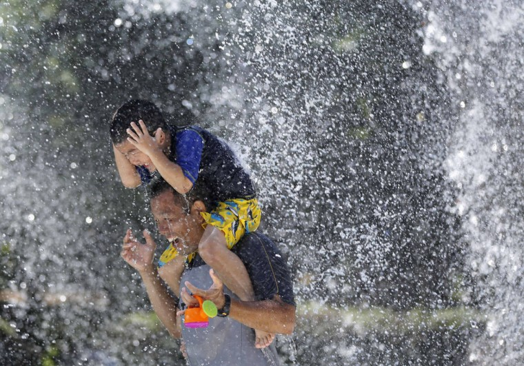 A boy sits on his father's shoulders as they cool down in the hot weather at a fountain in Tokyo August 5, 2014. The temperature rose to 36 degrees Celsius (96.8 degrees Fahrenheit) in the Japanese capital. (REUTERS/Toru Hanai)