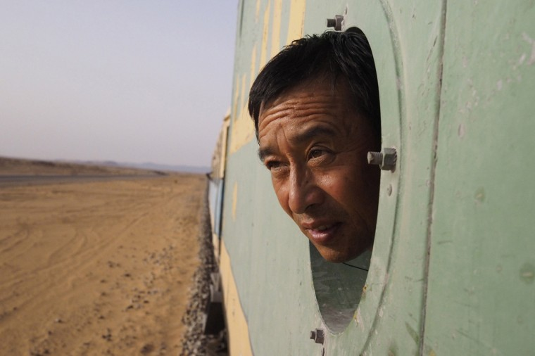 A Chinese businessman looks out the window while on board a SNIM train carrying iron ore and mine workers across the desert outside Zouerate June 24, 2014. (Joe Penney/Reuters)