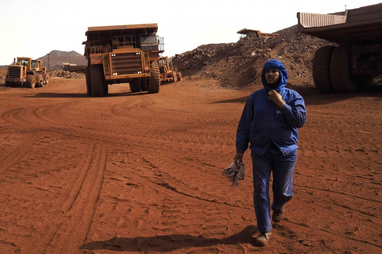 A SNIM truck driver walks in front of trucks at the TO-14 iron ore mine in Zouerate June 23, 2014. (Joe Penney/Reuters)