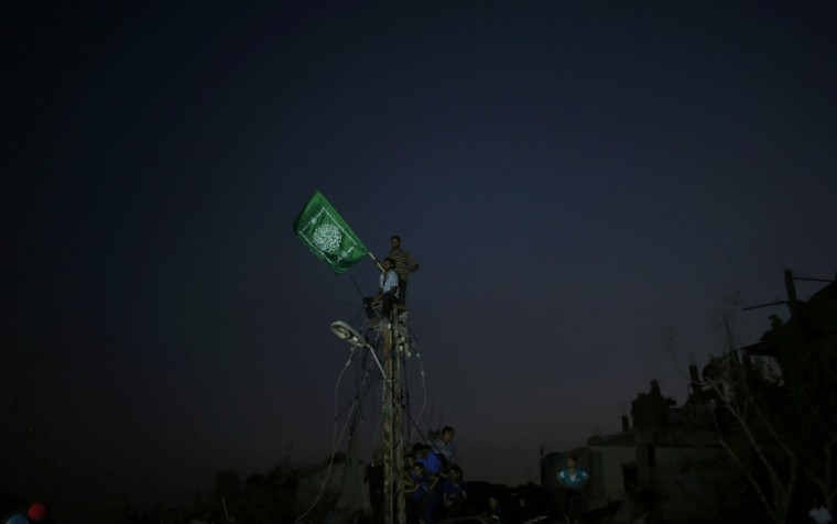 Palestinians stand atop an electrical pole after power was cut in the area during an Israeli offensive, in the Shejaia neighborhood east of Gaza City August 27, 2014. An open-ended ceasefire in the Gaza war held on Wednesday as Prime Minister Benjamin Netanyahu faced strong criticism in Israel over a costly conflict with Palestinian militants in which no clear victor emerged. (Mohammed Salem/Reuters)