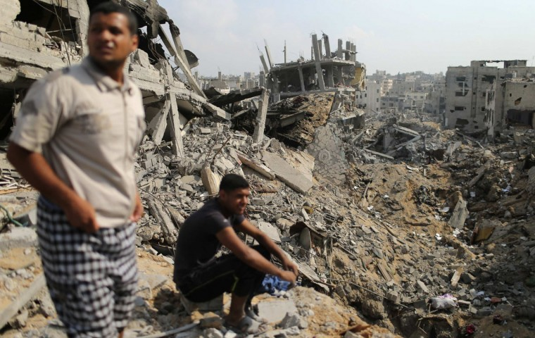 Palestinians look at destroyed houses after returning to the Shejaia neighbourhood, which witnesses said was heavily hit by Israeli shelling and air strikes during the Israeli offensive, in the east of Gaza City August 5, 2014. Israel pulled its ground forces out of the Gaza Strip on Tuesday and began a 72-hour truce with Hamas mediated by Egypt as a first step towards negotiations on a more enduring end to the month-old war. Gaza officials say the war has killed 1,834 Palestinians, most of them civilians. Israel says 64 of its soldiers and three civilians have been killed since fighting began on July 8, after a surge in Palestinian rocket launches. (REUTERS/Mohammed Salem)