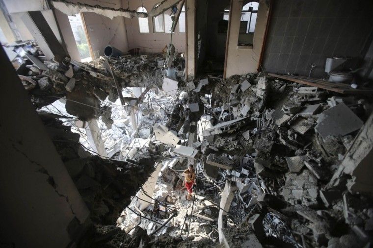 A Palestinian man inspects his house, which witnesses said was hit by an Israeli air strike, in Rafah in the southern Gaza Strip August 26, 2014. Israeli air strikes launched before dawn on Tuesday killed two Palestinians and destroyed much of one of Gaza's tallest apartment and office buildings, setting off huge explosions and wounding 20 people, Palestinian health officials said. Israel had no immediate comment on the attacks that took place as Egyptian mediators stepped up efforts to achieve an elusive ceasefire to end seven weeks of fighting. Israel launched an offensive on July 8, with the declared aim of ending rocket fire into its territory. (Ibraheem Abu Mustafa/Reuters)