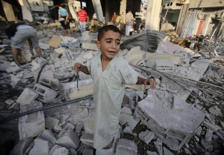 A Palestinian boy cries as he stands in a debris-strewn street near his family's house, which witnesses said was damaged by an Israeli air strike in Rafah in the southern Gaza Strip August 26, 2014. Israeli air strikes launched before dawn on Tuesday killed two Palestinians and destroyed much of one of Gaza's tallest apartment and office buildings, setting off huge explosions and wounding 20 people, Palestinian health officials said. Israel had no immediate comment on the attacks that took place as Egyptian mediators stepped up efforts to achieve an elusive ceasefire to end seven weeks of fighting. Israel launched an offensive on July 8, with the declared aim of ending rocket fire into its territory. (Ibraheem Abu Mustafa/Reuters)