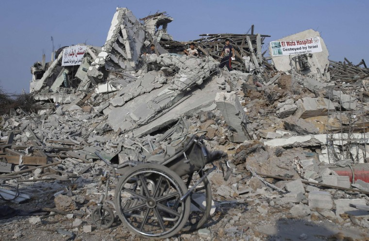 A wheelchair is seen as Palestinians stand atop the ruins of the headquarters of El-Wafa rehabilitation hospital, which witnesses said was destroyed during a seven-week Israeli offensive, in the east of Gaza City August 28, 2014. Patients receiving treatment in the hospital were moved to another branch of El-Wafa hospital, officials said. An open-ended ceasefire in the Gaza war held on Wednesday as Prime Minister Benjamin Netanyahu faced strong criticism in Israel over a costly conflict with Palestinian militants in which no clear victor has emerged. Israel launched an offensive on July 8, with the declared aim of ending rocket fire into its territory. (Ibraheem Abu Mustafa/Reuters)