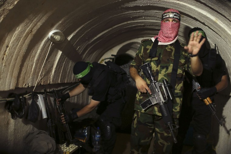 A Palestinian fighter from the Izz el-Deen al-Qassam Brigades, the armed wing of the Hamas movement, gestures inside an underground tunnel in Gaza August 18, 2014. A rare tour that Hamas granted to a Reuters reporter, photographer and cameraman appeared to be an attempt to dispute Israel's claim that it had demolished all of the Islamist group's border infiltration tunnels in the Gaza war. Picture taken August 18, 2014. (REUTERS/Mohammed Salem)