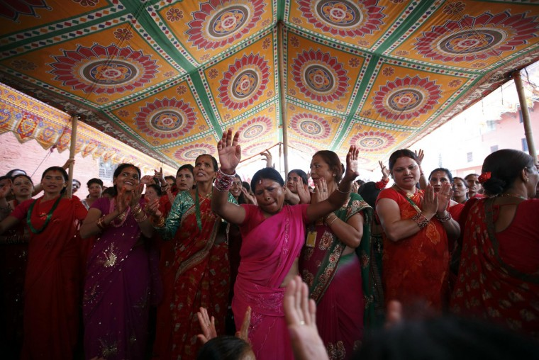 Women sing and dance at the premises of Pashupatinath Temple during the Teej festival in Kathmandu August 28, 2014. The three-day festival, commemorating the union of Goddess Parvati and Lord Shiva, involves sumptuous feasts and rigid fasting. Hindu women pray for marital bliss, the well-being of their spouses and children, and the purification of their own bodies and souls during this period of religious fasting. (Navesh Chitrakar/Reuters)