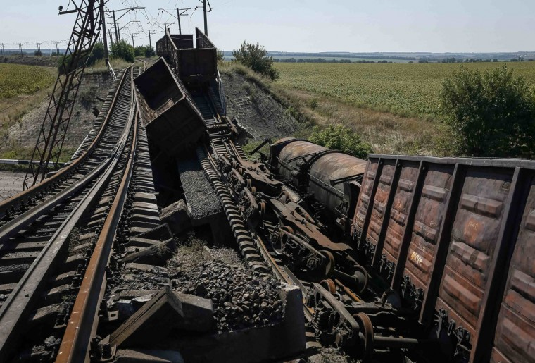 Train wagons are seen on the destroyed railway bridge which collapsed during the fighting between the Ukrainian army and pro-Russian separatists, over a main road leading to the eastern Ukrainian city of Donetsk, near the village of Novobakhmutivka, north of Donetsk city. (Gleb Garanich/Reuters)