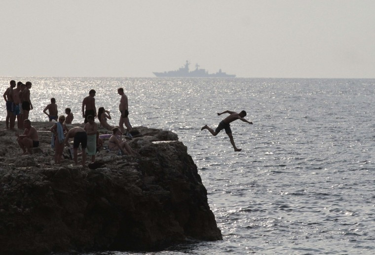 A man jumps into the waters of the Black Sea, with a Russian warship seen in the background, in Sevastopol, Crimea. Russian President Vladimir Putin, senior government officials and many lawmakers will visit Crimea this week, two sources told Reuters, in a defiant show of support for Russia's annexation of the Black Sea region despite tough new Western economic sanctions. A source from the pro-Kremlin United Russia party said most of the 450 lawmakers from the State Duma lower house of parliament were expected to join Putin and Prime Minister Dmitry Medvedev in Crimea for talks on August 14. Crimea, famed for its lush climate, summer resorts and rich literary associations, is largely populated by ethnic Russians. Moscow presented the region as a gift to Ukraine from Russia in the 1950s when both were firmly united within the Soviet Union. (Pavel Rebrov/Reuters)