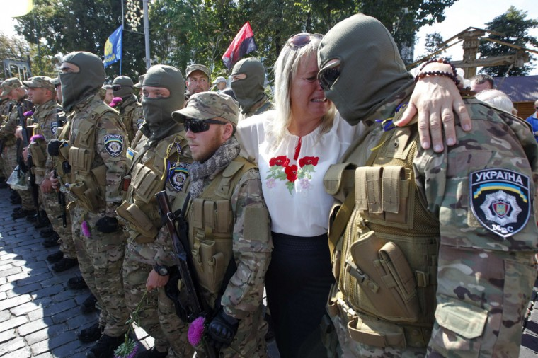 """A woman reacts as she embraces her son, who joined as a new volunteer of the Ukrainian interior ministry's special battalion """"Sich"""", before a ceremony, where he and his comrades will take an oath of allegiance to the country, in Kiev August 26, 2014. (Valentyn Ogirenko/Reuters)"""
