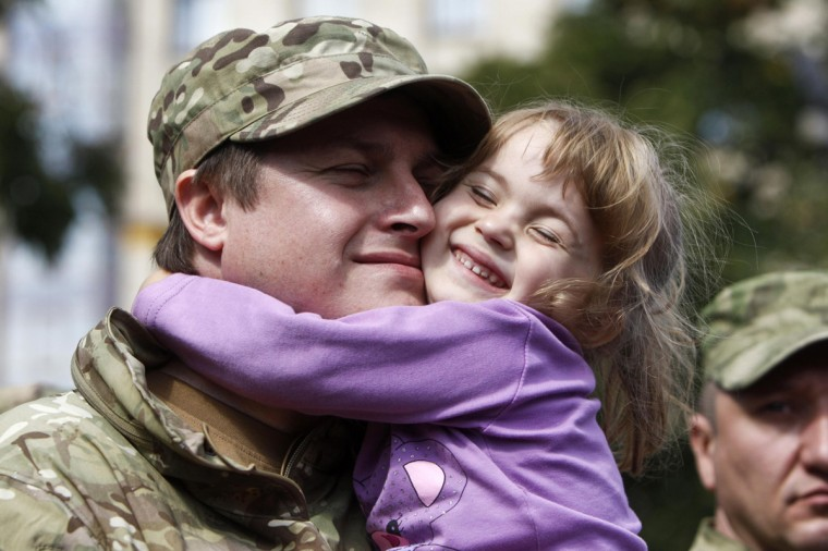 """A new volunteer of the Ukrainian interior ministry's special battalion """"Sich"""" embraces his daughter during a ceremony, where he and his comrades will take an oath of allegiance to the country, in Kiev August 26, 2014. (Valentyn Ogirenko/Reuters)"""