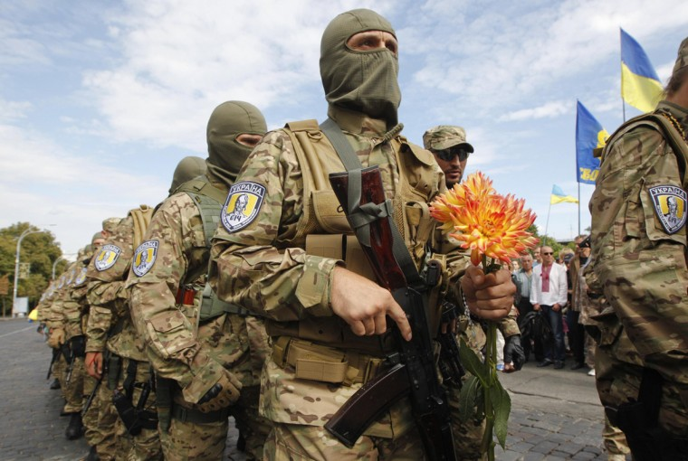 """A new volunteer of the Ukrainian interior ministry's special battalion """"Sich"""" holds flowers during a ceremony, where he and his comrades will take an oath of allegiance to his country, in Kiev August 26, 2014. (Valentyn Ogirenko/Reuters)"""