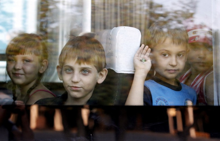 Children who have fled the fighting in eastern regions of Ukraine look out from a mini-bus upon their arrival at a railway station, before leaving for their temporary accommodation, in Stavropol, southern Russia, August 21, 2014. (Eduard Korniyenko/Reuters)