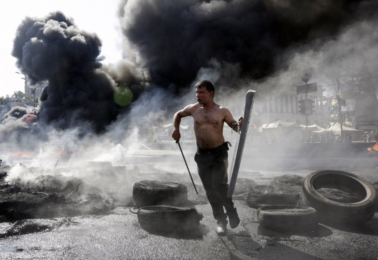 A protester runs during clashes with pro-government forces at Independence Square in Kiev August 7, 2014. Tensions flared on Thursday on Kiev's Independence Square, the scene of street protests that toppled a Moscow-backed president in February, when protesters still camped there clashed with city workers who tried to clear away their tents. (Konstantin Chernichkin/Reuters)