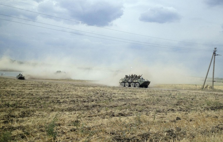 Servicemen sit atop an armoured vehicle as they travel through the steppe near the village of Krasnodarovka in Rostov region August 28, 2014. A Reuters reporter saw on Thursday a column of armoured vehicles and dust-covered troops, one of them with an injured face, driving through the Russian steppe just across the border from a part of Ukraine which Kiev says is occupied by Russian troops. None of the men or vehicles had standard military identification marks, but the reporter saw a Mi-8 helicopter with a red star insignia -- consistent with Russian military markings -- land next to a nearby military first aid tent. The column was driving east away from the Ukrainian border across open countryside near the village of Krasnodarovka in Russia's Rostov region. (Maria Tsvetkova/Reuters)