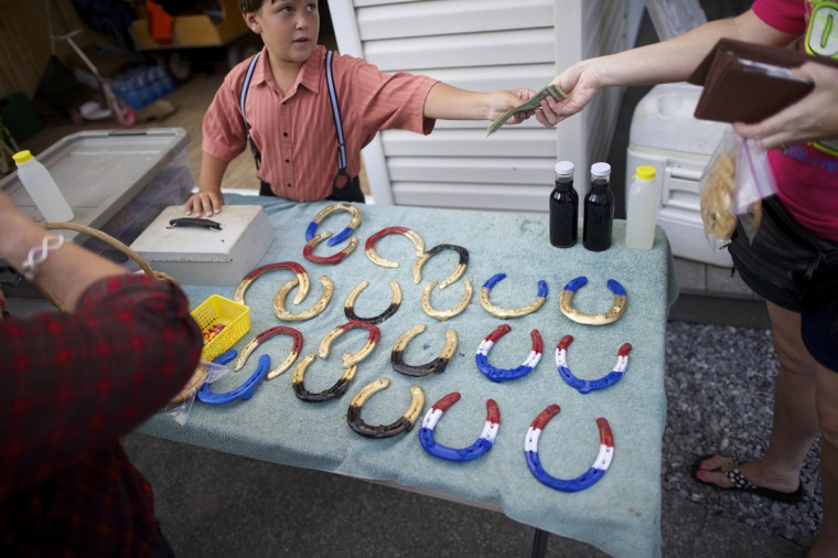 An Amish boy sells painted horseshoes to tourists in Lancaster County, Pennsylvania August 9, 2014. (Mark Makela/Reuters)