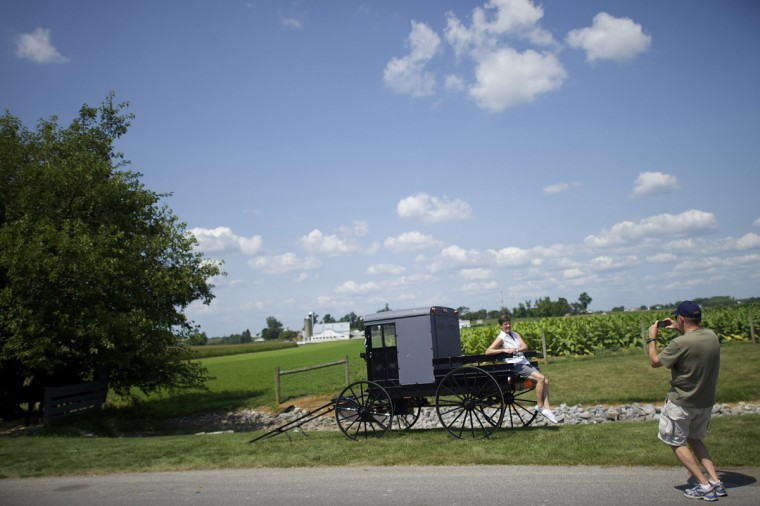 Dan Roller photographs his wife, Sharon, seated on a buggy, at the Amish Experience, a tourism destination in the village of Bird-in-Hand, Pennsylvania August 9, 2014. (Mark Makela/Reuters)