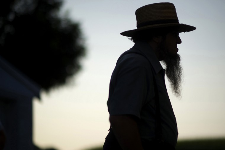 A silhouetted Amish man waits during his buggy tour in Lancaster County, Pennsylvania August 9, 2014. It's that Old World charm of the Amish that draws 8 million tourists - and $1.9 billion - each year to Pennsylvania's Lancaster County, home of the nation's largest Amish community of 31,000. (Mark Makela/Reuters)