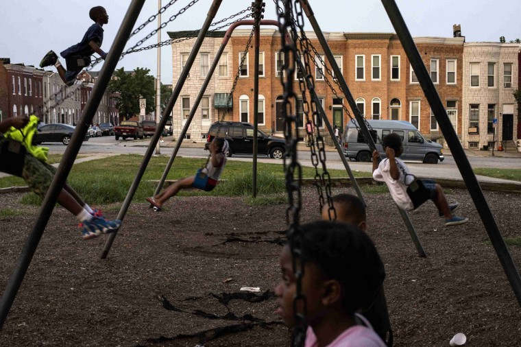 Children play on swings at Collington Square Park an hour before a curfew law took effect in Baltimore August 8, 2014. Mayor Stephanie Rawlings-Blake said the measure, which took effect on Friday, was aimed at getting children off the streets before they were put in danger. (James Lawler Duggan/Reuters)
