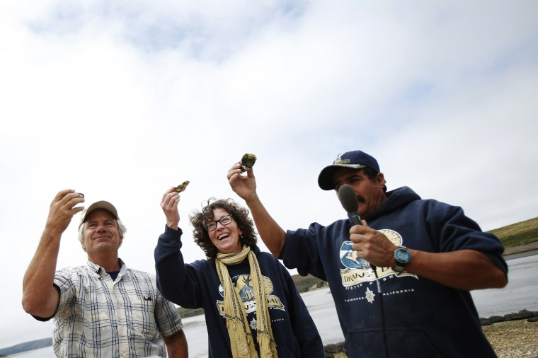 (L-R) Drakes Bay Oysters Company owner Kevin Lunny, his wife Nancy Lunny and production manager Jorge Mata lead an oyster toast during a celebration event at Drakes Bay Oyster Company in Inverness, California July 31, 2014. (Stephen Lam/Reuters)