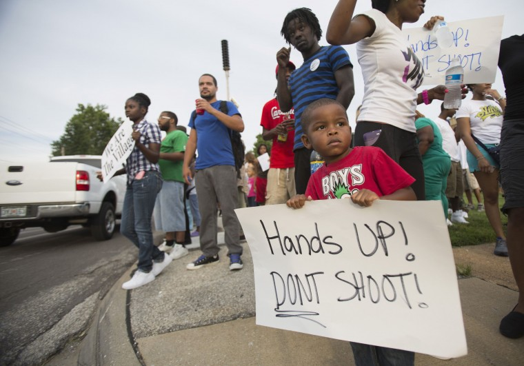 Romel Turner, 3, holds a sign during a peaceful demonstration at Great St. Mark Family Church, as communities react to the shooting of Michael Brown in St. Louis, Missouri August 14, 2014. Missouri's governor Jay Nixon moved on Thursday to calm days of racially charged protests over the police shooting of Brown, an unarmed black teenager, naming the African-American captain of the Highway Patrol Ron Johnson to oversee security in the St. Louis suburb of Ferguson. (Mario Anzuoni/Reuters)