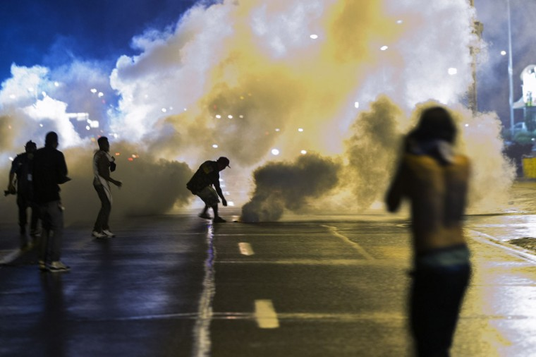 A protester reaches down to throw back a smoke canister as police clear a street after the passing of a midnight curfew meant to stem ongoing demonstrations in reaction to the shooting of Michael Brown in Ferguson, Missouri August 17, 2014. The group of protesters angry at the shooting death of Brown, a black teenager, by a white police officer remained on the streets of Ferguson, Missouri, early on Sunday minutes past the declared curfew, as police gathered nearby in a tense standoff. (Lucas Jackson/Reuters)