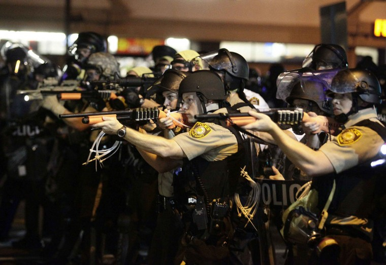 Police officers point their weapons at demonstrators protesting against the shooting death of Michael Brown in Ferguson, Missouri August 18, 2014. Police fired tear gas and stun grenades at protesters on Monday after days of unrest sparked by the fatal shooting of unarmed black teenager Michael Brown by a white policeman. (REUTERS/Joshua Lott)