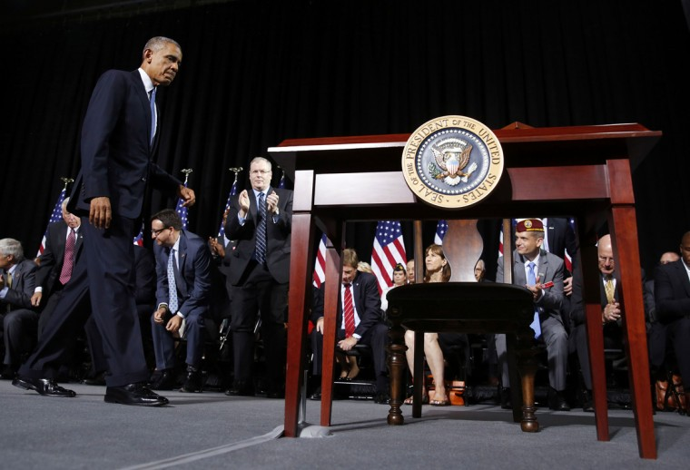U.S. President Barack Obama walks over to sign H.R. 3230, the Veteran's Access to Care through Choice, Accountability and Transparency Act of 2014, while at Ft. Belvoir, Virginia, August 7, 2014. (Larry Downing/Reuters)