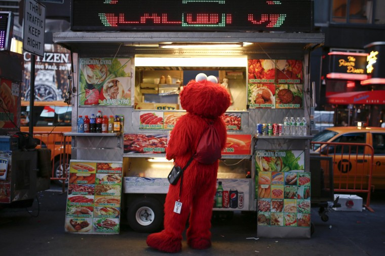 Jorge, an immigrant from Mexico, and dressed as the Sesame Street character Elmo, buys food from a street food cart in Times Square, New York July 30, 2014. (Eduardo Munoz/Reuters)