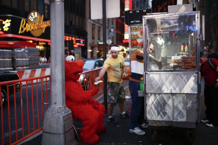 Jorge, an immigrant from Mexico, dressed as the Sesame Street character Elmo, exchanges his tips for larger bills from a street food car vendor in Times Square, New York July 30, 2014. (Eduardo Munoz/Reuters)