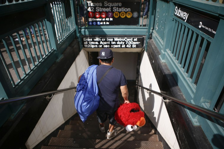 Jorge, an immigrant from Mexico, who dresses as the Sesame Street character Elmo, heads into a subway station after making tips for photographs in Times Square, New York July 30, 2014. (Eduardo Munoz/Reuters)