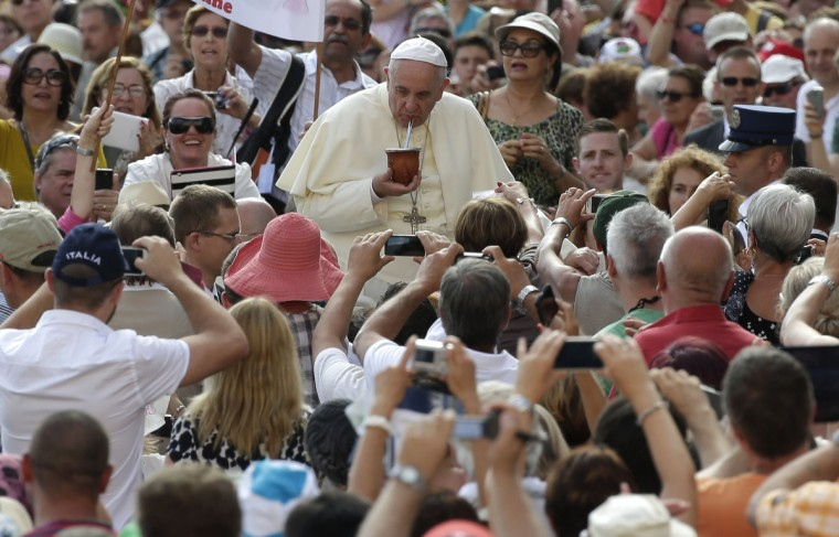 Pope Francis drinks a traditional South American drink called mate offered by the faithful as he arrives to lead his weekly audience in Saint Peter's Square at the Vatican. (Max Rossi//Reuters)