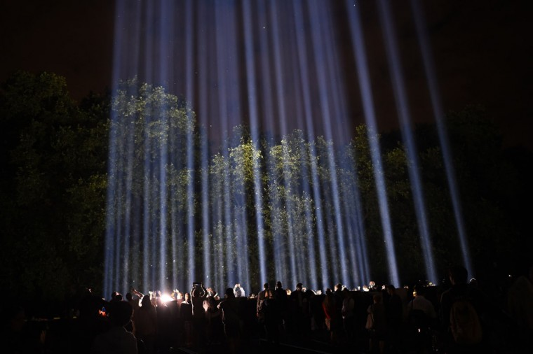 "People enjoy an artwork entitled ""Spectra"" by Japanese visual artist Ryoji Ikeda during ""Lights Out"", as part of commemorations to mark the 100th anniversary of the outbreak of World War One (WWI), in London August 4, 2014. Lights across Britain were being switched off for an hour on Monday night in a tribute to the dead of World War One, inspired by the prophetic observation of Britain's foreign minister on the eve of war 100 years ago. Spectra's illuminations will light up the London skyline for seven nights. (REUTERS/Dylan Martinez)"