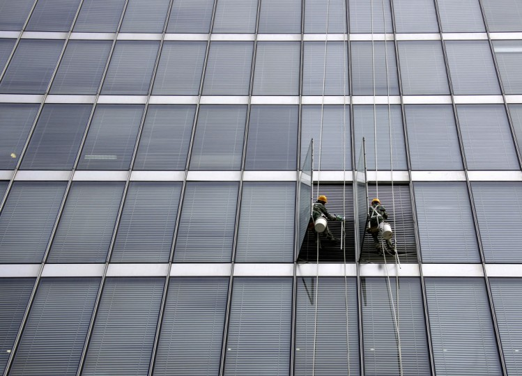Cleaners open windows as they abseil the front of a building in the financial district of Beijing on August 3, 2009. (REUTERS/David Gray)
