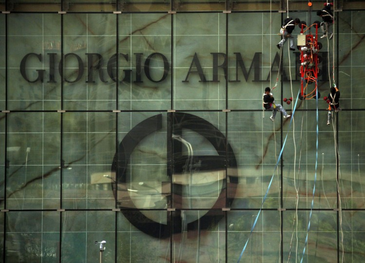 Cleaners abseil down the front of a shopping mall displaying the logo of Italian fashion label Giorgio Armani in central Beijing on June 26, 2011. (REUTERS/David Gray)