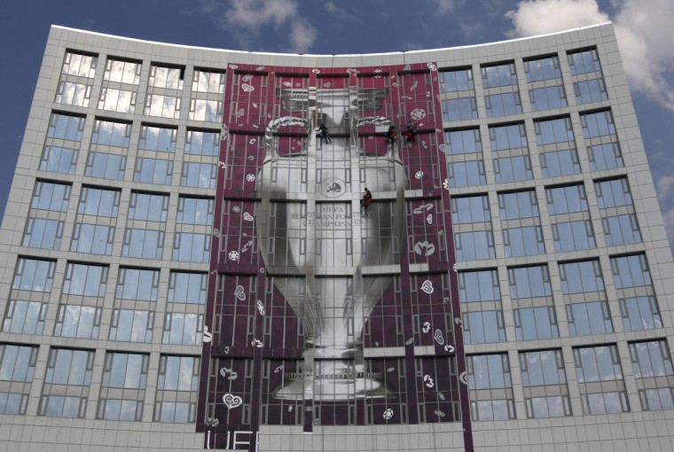 Workers abseil as they attach a huge placard displaying the Euro 2012 trophy as they decorate a building near the Olympic stadium in central Kiev on June 6, 2012. (REUTERS/Alexander Demianchuk)