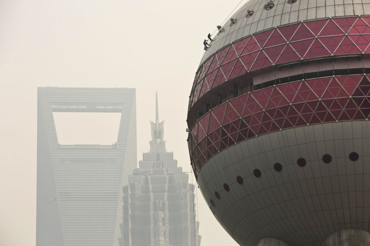 Workers clean the exterior of the Oriental Pearl TV Tower during a hazy day at Lujiazui financial district of Pudong in Shanghai on March 10, 2014. (REUTERS/Aly Song)