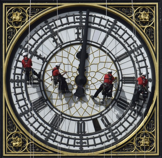 Cleaners abseil down one of the faces of Big Ben, to clean and polish the clock face, above the Houses of Parliament, in central London on August 19, 2014. (REUTERS/Toby Melville)