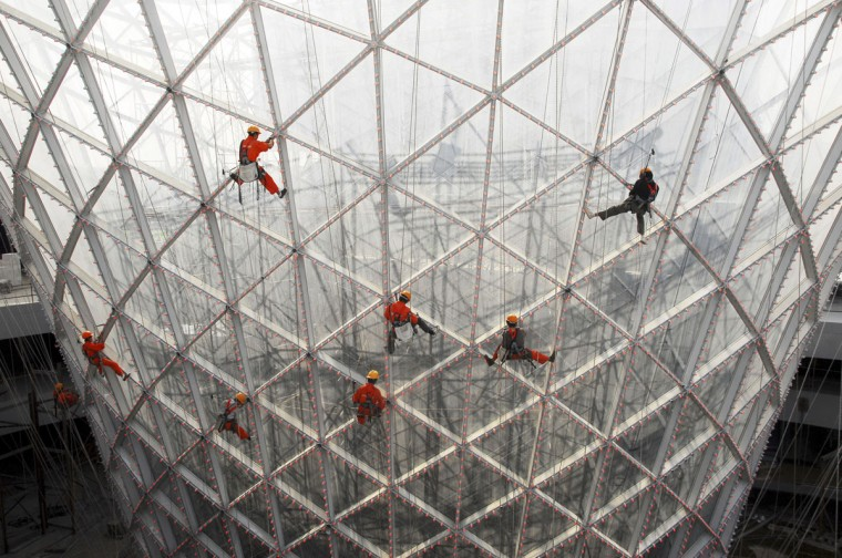 """Workers clean the exterior of the """"Sun Valley"""" at the 2010 World Expo site in Shanghai on October 10, 2009. (REUTERS/China Daily)"""