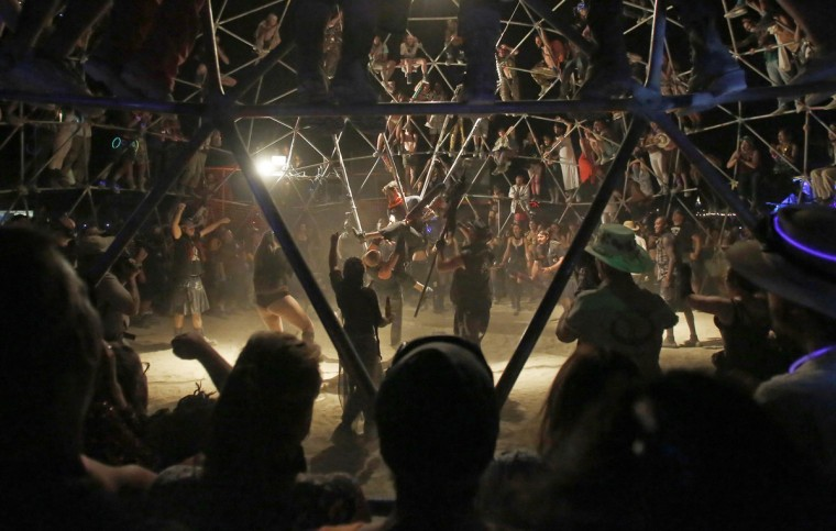 "A crowd watches as two fighters battle in the Thunderdome during the Burning Man 2014 ""Caravansary"" arts and music festival in the Black Rock Desert of Nevada, August 27, 2014. People from all over the world have gathered at the sold out festival to spend a week in the remote desert cut off from much of the outside world to experience art, music and the unique community that develops. (Jim Urquhart/Reuters)"
