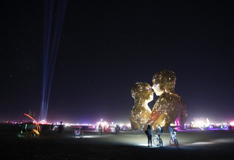 "People look at the art installation Embrace during the Burning Man 2014 ""Caravansary"" arts and music festival in the Black Rock Desert of Nevada, August 27, 2014. People from all over the world have gathered at the sold out festival to spend a week in the remote desert cut off from much of the outside world to experience art, music and the unique community that develops. (Jim Urquhart/Reuters)"