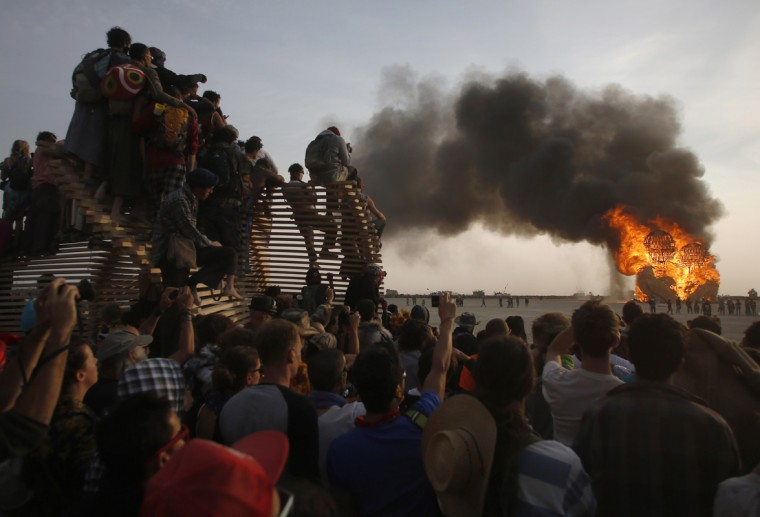 "Participants watch the art installation Embrace burn during the Burning Man 2014 ""Caravansary"" arts and music festival in the Black Rock Desert of Nevada, August 29, 2014. (Jim Urquhart/Reuters)"