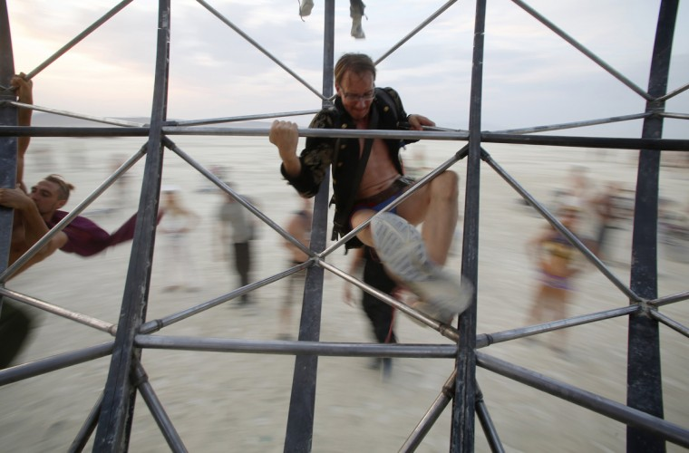 "A participant climbs onto the Eidolon Panspermia Ostentatia Duodenum (EPOD) spinning art installation during the Burning Man 2014 ""Caravansary"" arts and music festival in the Black Rock Desert of Nevada, August 28, 2014. (Jim Urquhart/Reuters)"