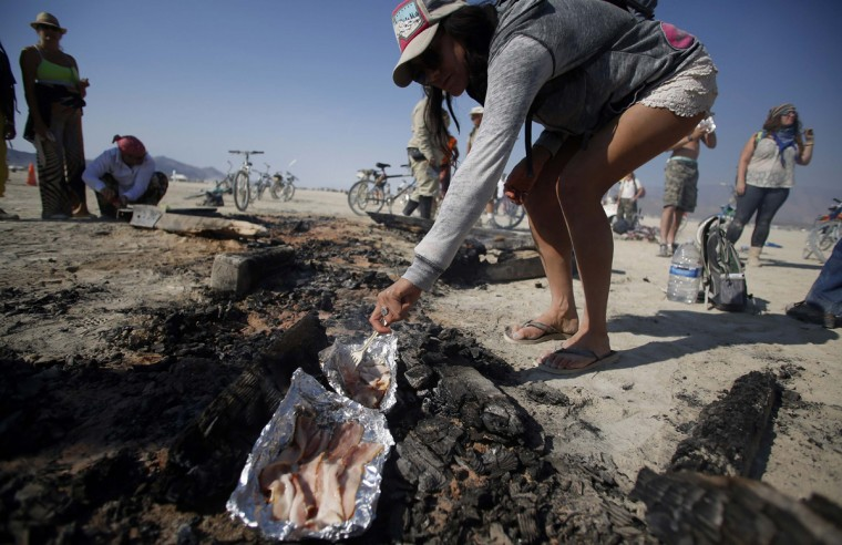 "Gina Krauss cooks bacon on the coals of the Man on the last day of the Burning Man 2014 ""Caravansary"" arts and music festival in the Black Rock Desert of Nevada, August 31, 2014. (Jim Urquhart/Reuters)"