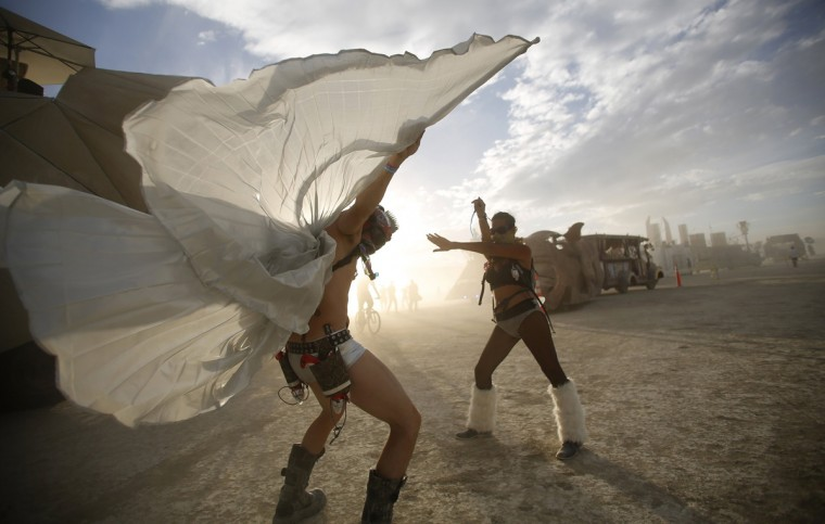 "Dillon Bracken (L) and Atalya Stachel dance during the Burning Man 2014 ""Caravansary"" arts and music festival in the Black Rock Desert of Nevada, August 30, 2014. (Jim Urquhart/Reuters)"