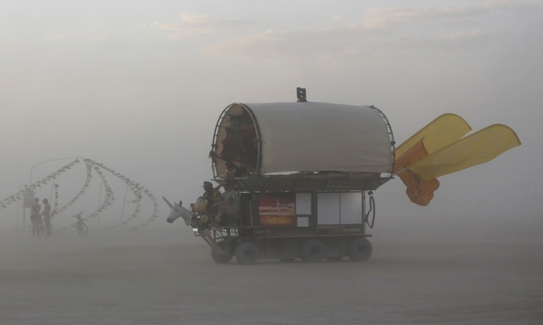 "A mutant vehicle drives through a dust storm during the Burning Man 2014 ""Caravansary"" arts and music festival in the Black Rock Desert of Nevada, August 29, 2014. (Jim Urquhart/Reuters)"