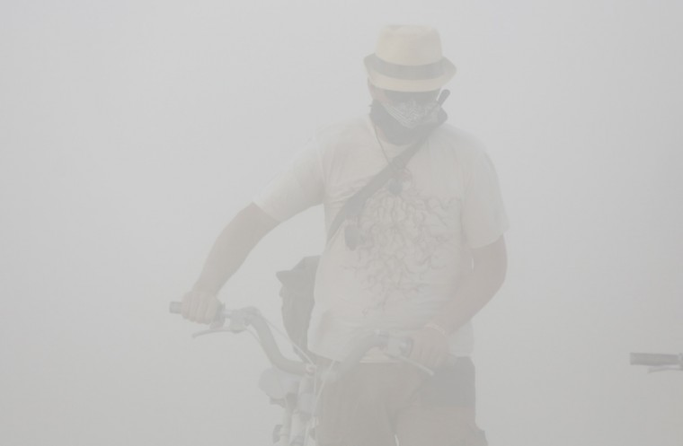 "Christoffer McCollom navigates a dust storm during the Burning Man 2014 ""Caravansary"" arts and music festival in the Black Rock Desert of Nevada, August 29, 2014. (Jim Urquhart/Reuters)"