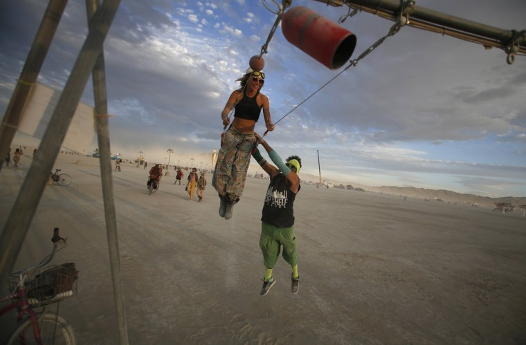 "Gwen Barker (L) and Rezwan Khan play on a swing art installation during the Burning Man 2014 ""Caravansary"" arts and music festival in the Black Rock Desert of Nevada, August 30, 2014. (Jim Urquhart/Reuters)"