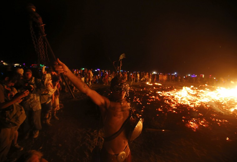 "A participant dances as the Temple of Grace burns on the last day of the Burning Man 2014 ""Caravansary"" arts and music festival in the Black Rock Desert of Nevada, August 31, 2014. (Jim Urquhart/Reuters)"